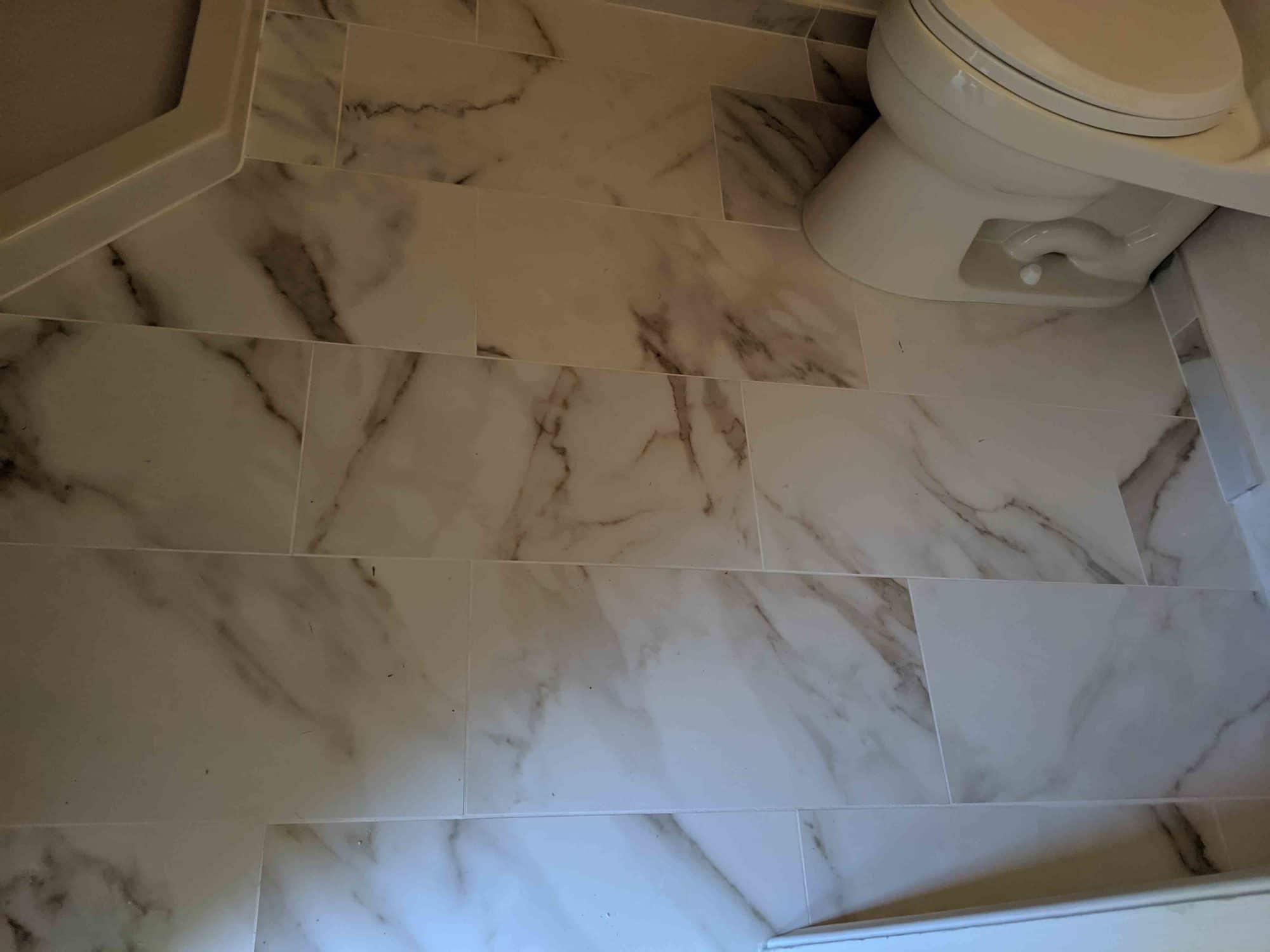 12x24 polished porcelain tile and fiberglass neo angle shower pan And tile floor.